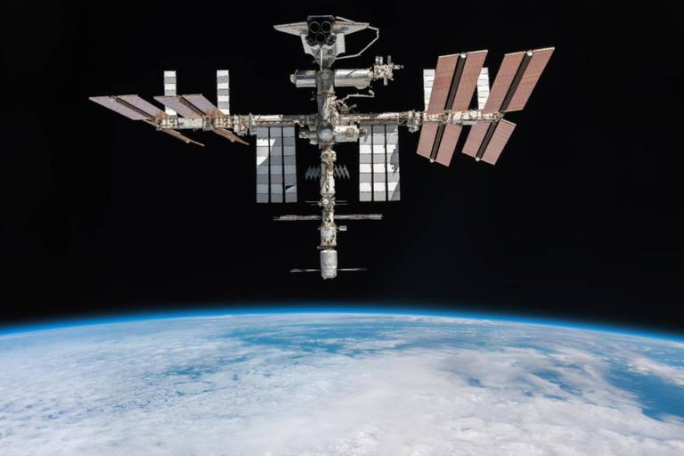 La ISS con el transbordador Endeavour en una de sus plataformas y al fondo el horizonte de la Tierra