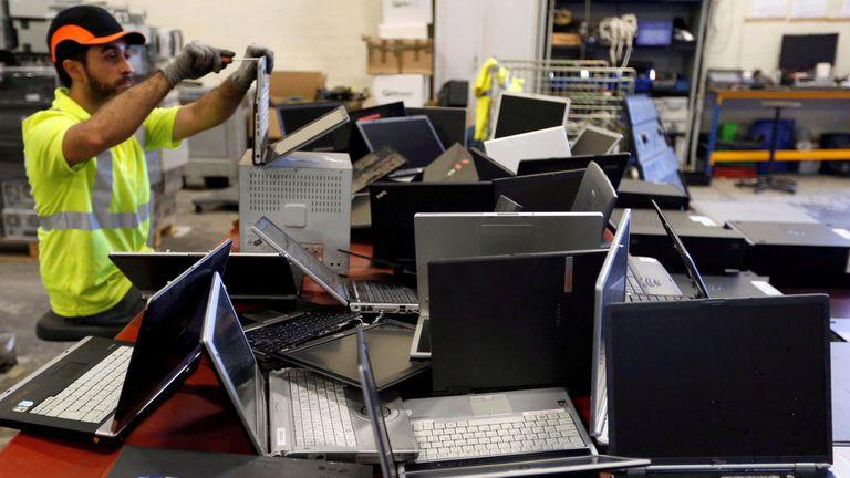 Un operario desarma notebooks para su procesamiento como basura electrónica en una planta cerca de Bordeaux, Francia