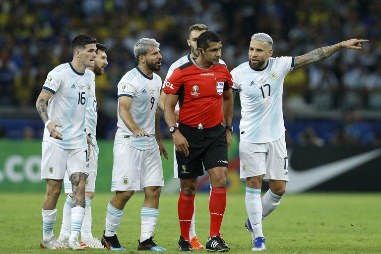 Nicolas Otamendi y Sergio Agüero le reclaman al árbitro Roddy Zambrano, de discreto desempeño en la semifinal contra Brasil