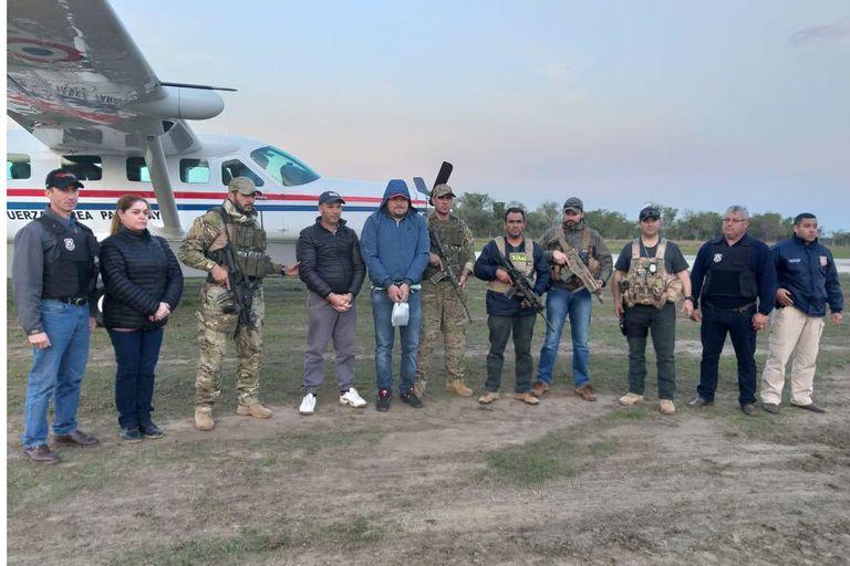 El detenido Saucedo, con capucha, rodeado por los agentes paraguayos que lo atraparon