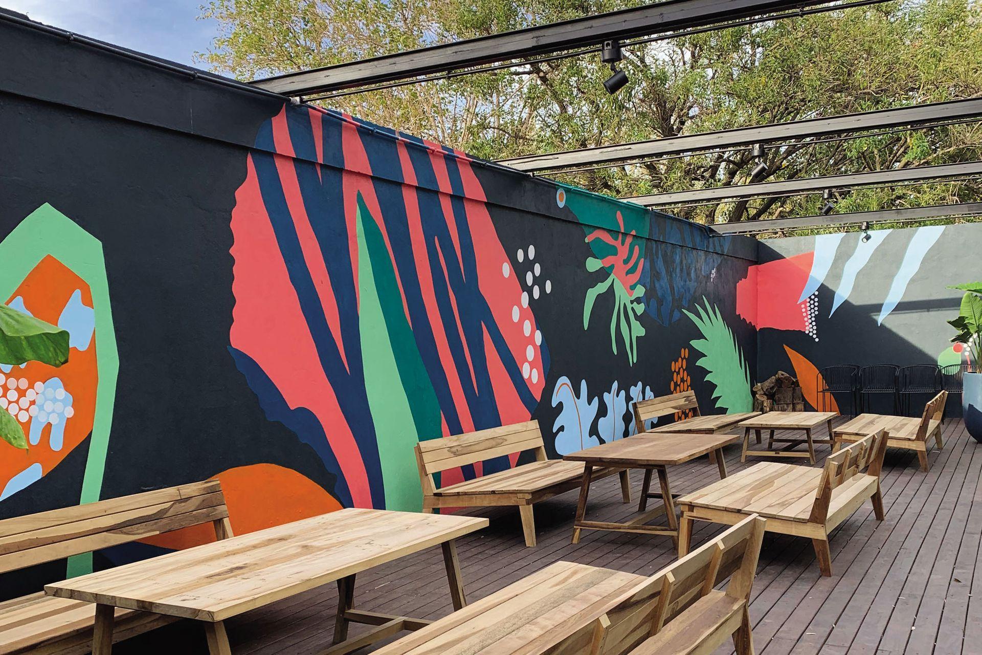 Rectas y curvas se combinan y recrean fragmentos de distintos elementos de la naturaleza, en este mural realizado por el artista Darío Parvis sobre las paredes perimetrales del patio del restaurante Enero.