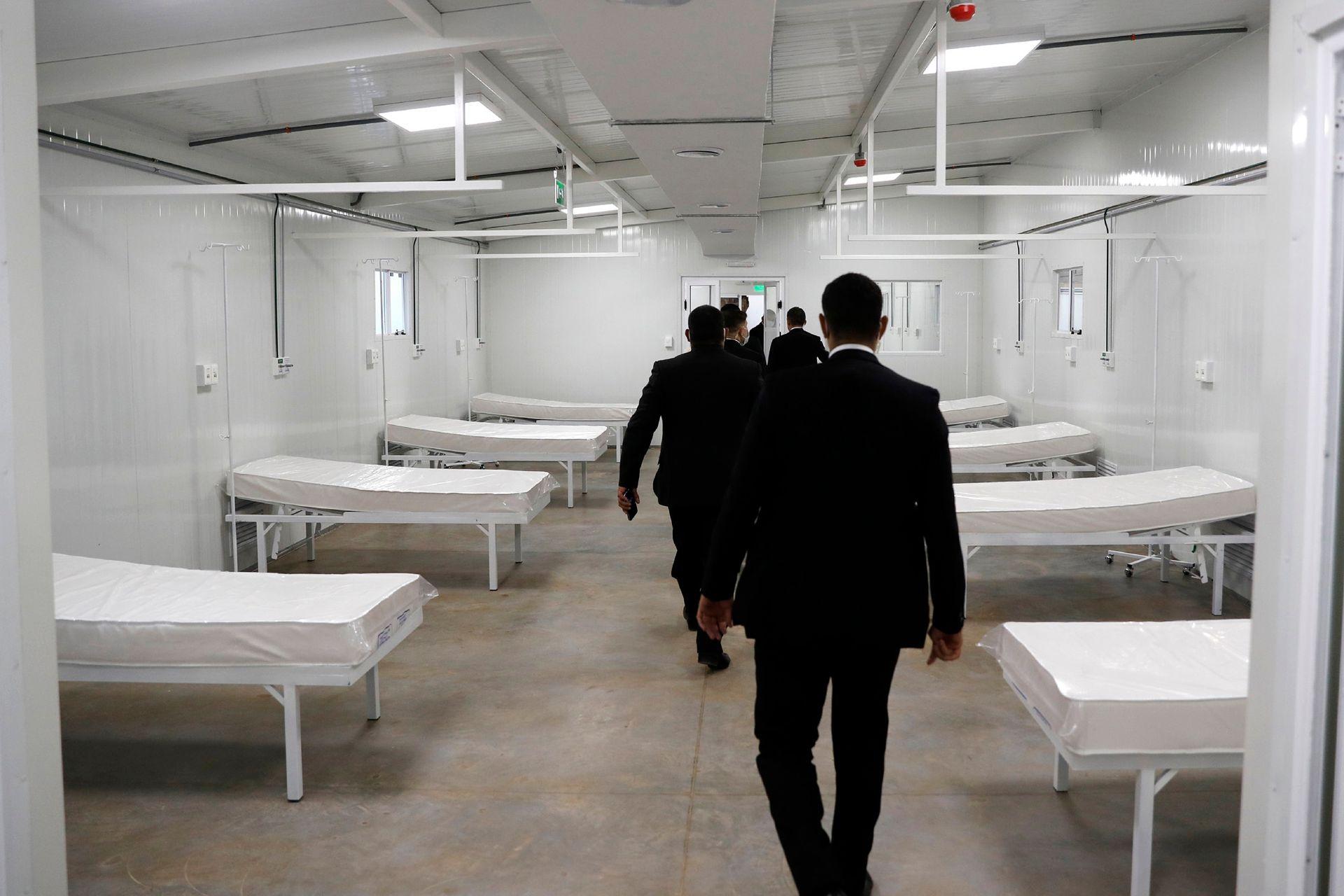 Los guardias de seguridad siguen al presidente de Paraguay mientras recorre una nueva instalación médica que recibirá a personas con COVID-19 en Itagua, Paraguay