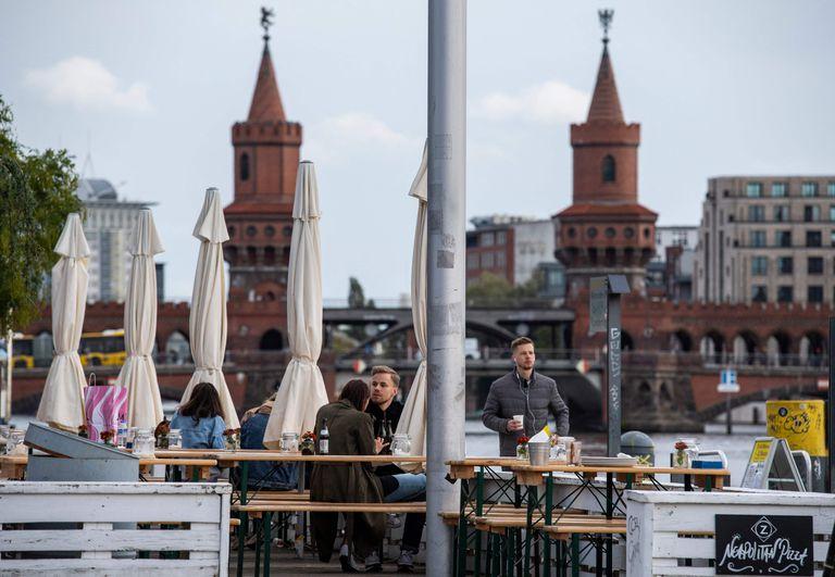 En esta foto de archivo tomada el 10 de octubre de 2020, la gente se sienta en una terraza con vista al río Spree y al Oberbaumbruecke en Berlín.