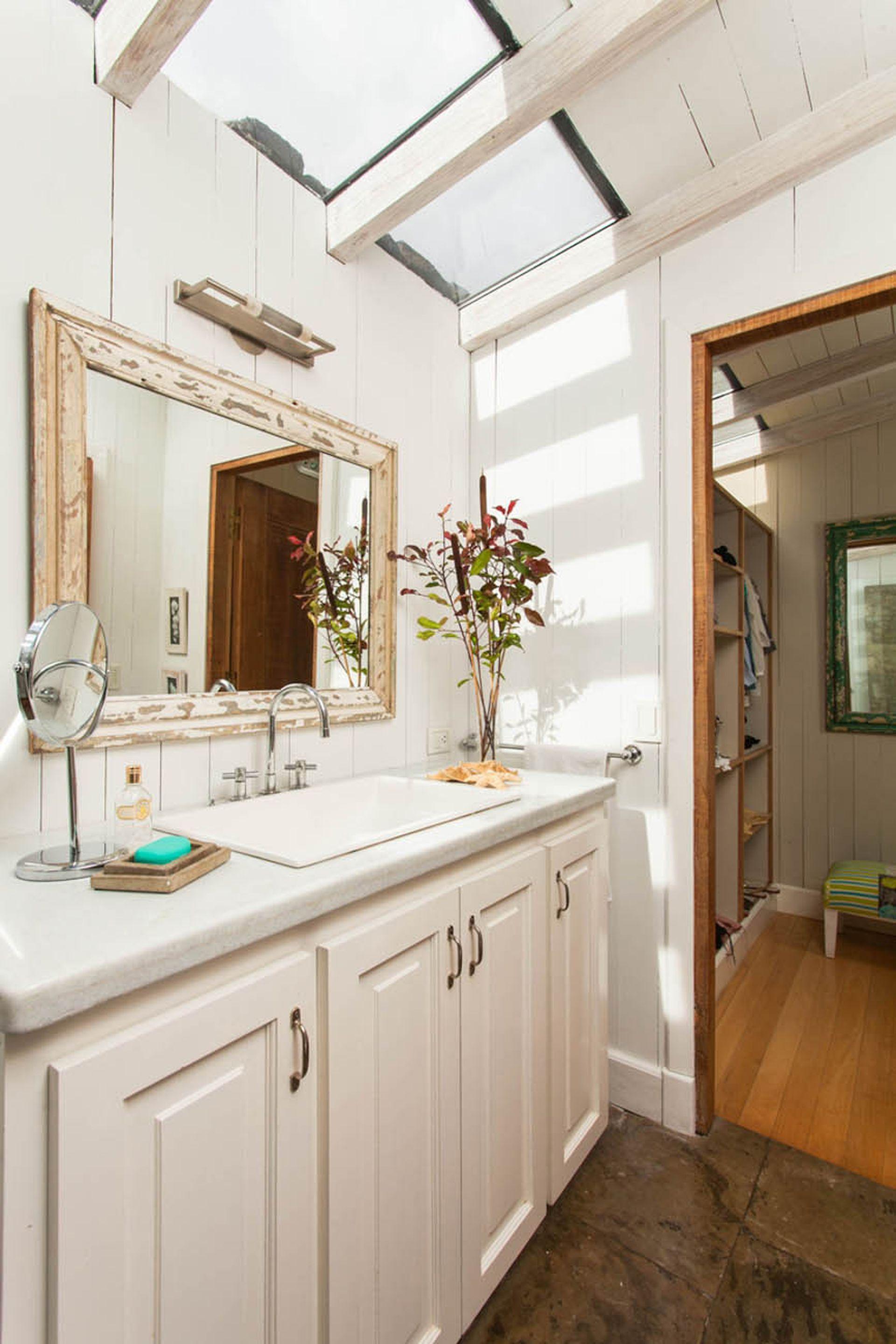 El baño, en blanco, también tiene techo de vidrio. Luego, en la zona húmeda, hay un deck de madera.