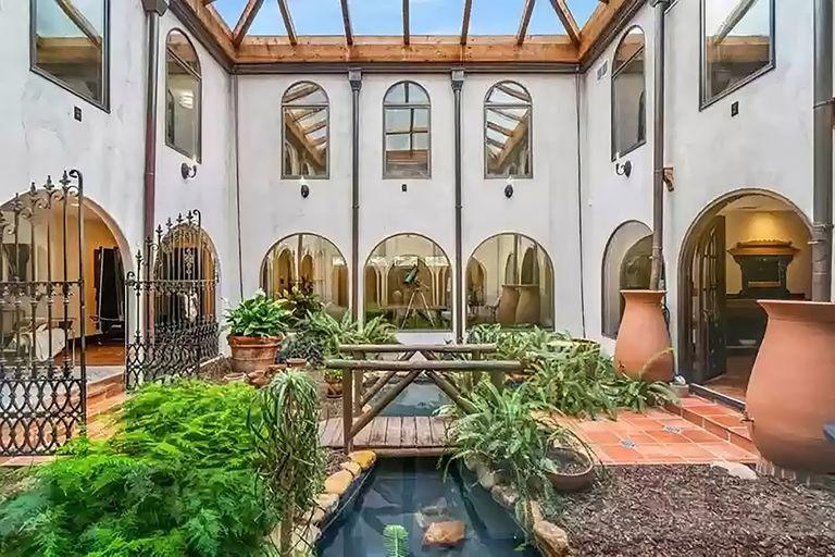 La casa tiene un atrio interior de dos pisos con estanque y jardines