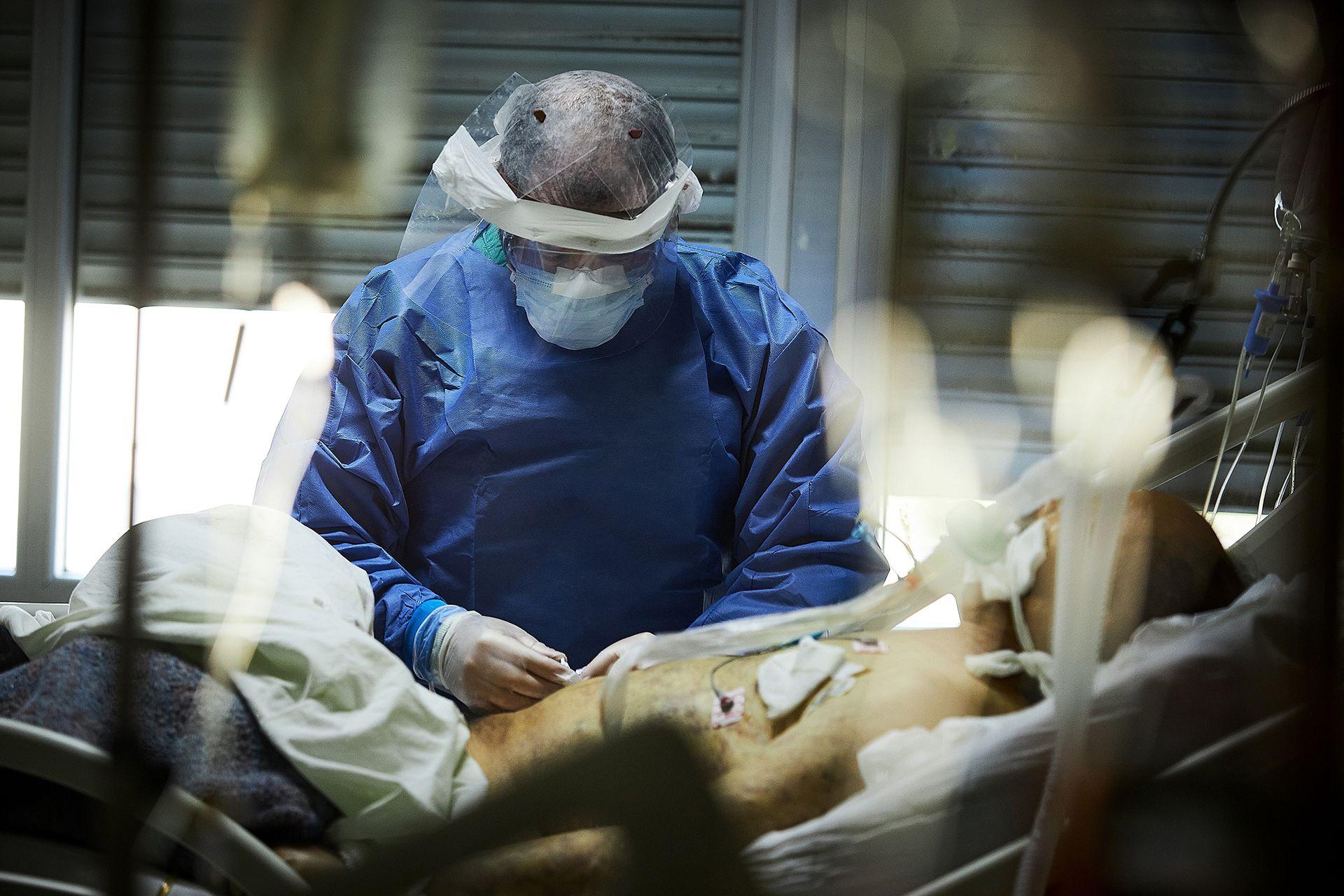 Uno de los enfermeros asiste a un paciente en terapia intensiva