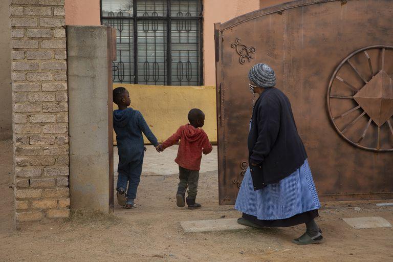 Una mujer mayor y dos niños entran a la casa de Gosiame Thamara Sithole en Tembisa, cerca de Johannesburgo, el jueves 10 de junio de 2021. (AP Foto/Denis Farrell)