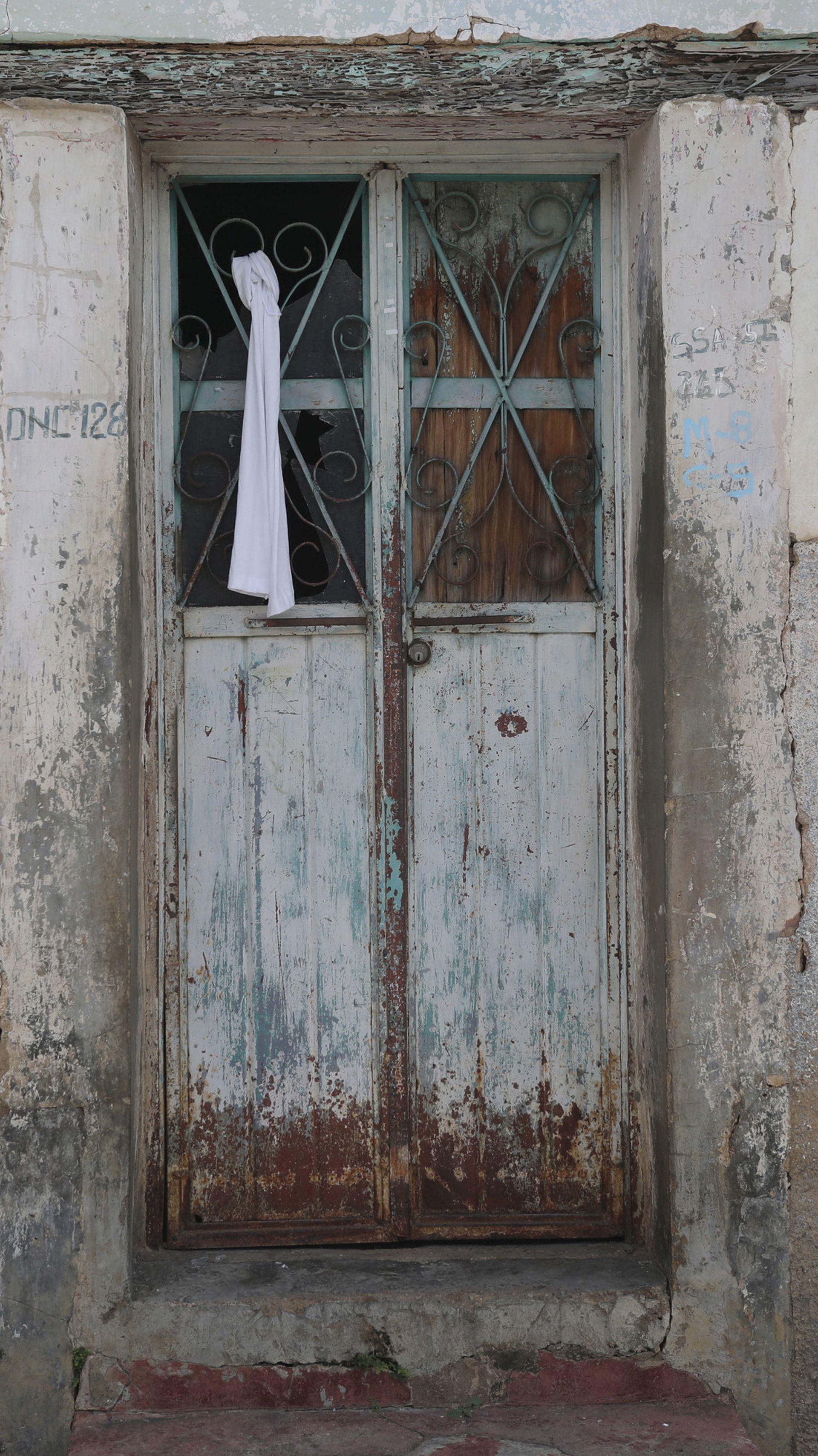 """Una bandera blanca está atada a la ventana de una casa mientras autoridades locales y líderes del grupo de autodefensa conocido como """"El Machete"""" se reúnen en Pantelho, estado de Chiapas"""
