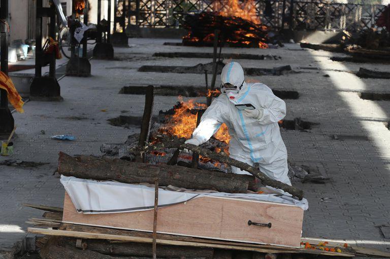 Un hombre lleva a cabo ritos funerarios en el cadáver de un familiar fallecido por COVID-19, en un crematorio en Jammu, India, el 23 de abril de 2021. (AP Foto/Channi Anand)