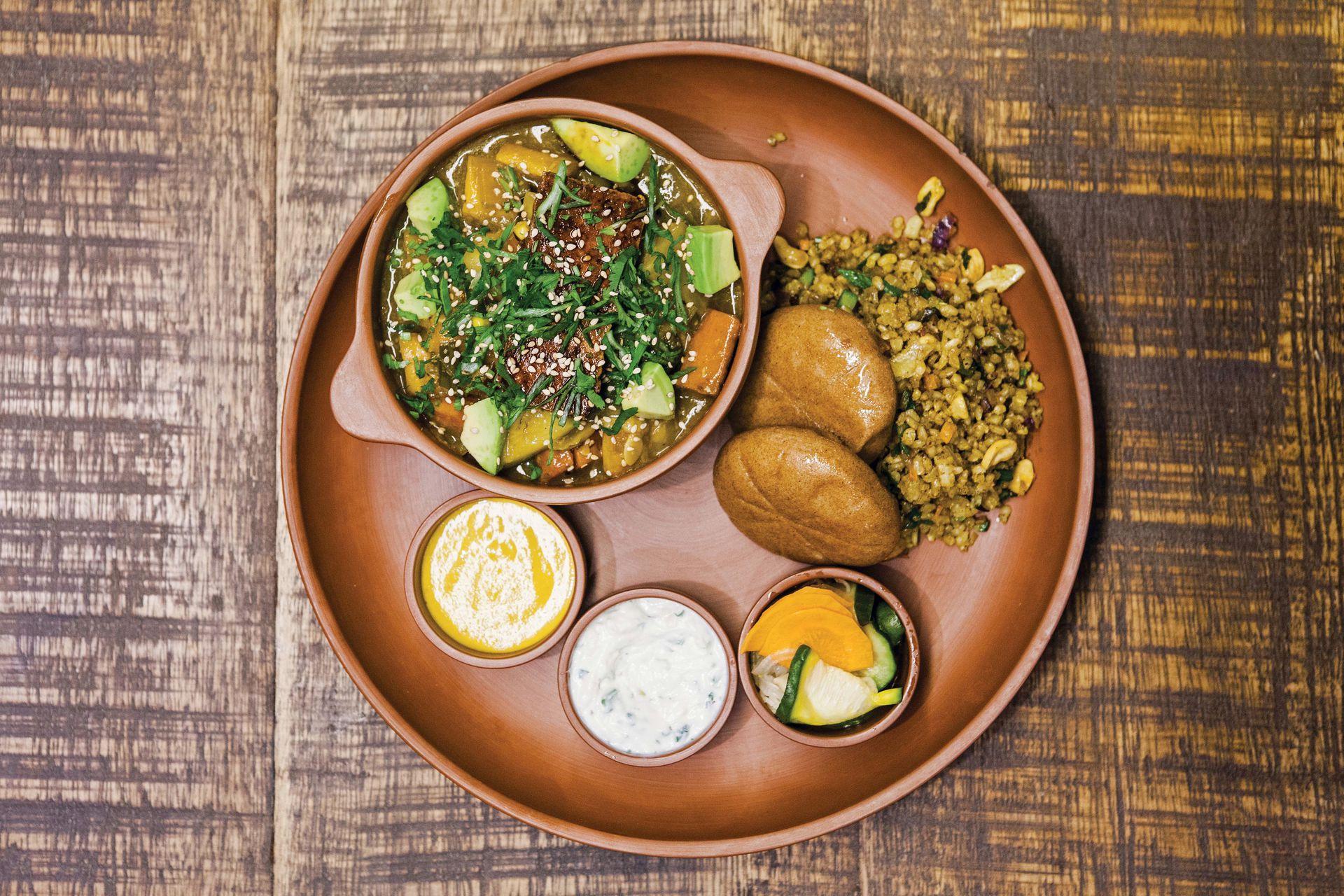 Curry de verduras con tofu laqueado en salsa teriyaki y palta, con dips de salsas picantes y pickles.