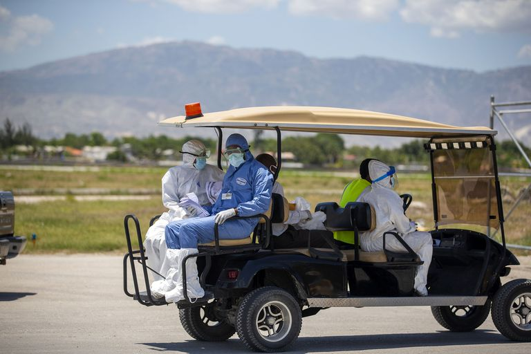 Trabajadores de la salud se alejan en un móvil después de controlar la temperatura corporal de los haitianos deportados que llegan de los Estados Unidos, en el Aeropuerto Internacional Toussaint Louverture en Port-au-Prince, Haití