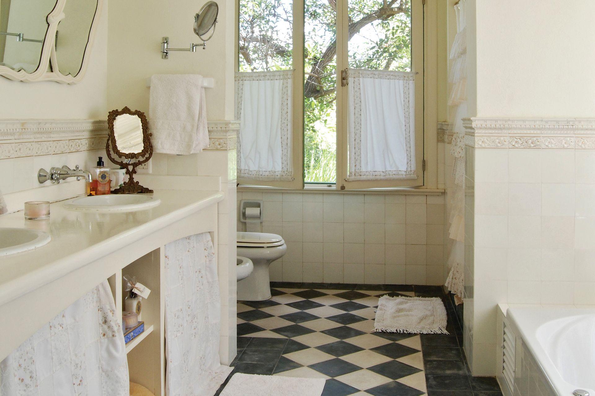 Pisos en damero y espejos de antaño para darle una impronta antigua al baño. ,