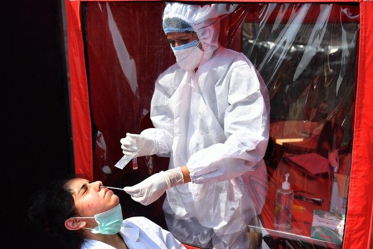 Una trabajadora de la salud toma una muestra de hisopado de un colega en una cabina portátil de un laboratorio móvil para realizar pruebas de coronavirus RT-PCR en Mumbai el 11 de febrero de 2021