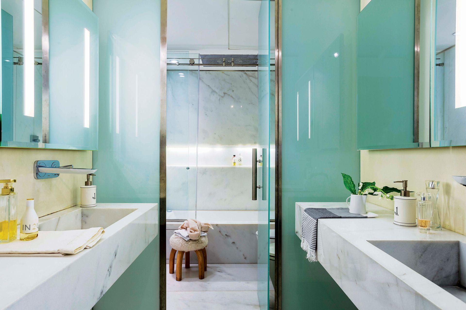 El baño de la suite tiene mesadas y revestimiento de mármol (Oscar Revestimientos), grifería cromada (Hansgrohe) y mampara de vidrio (Centro Cristales).