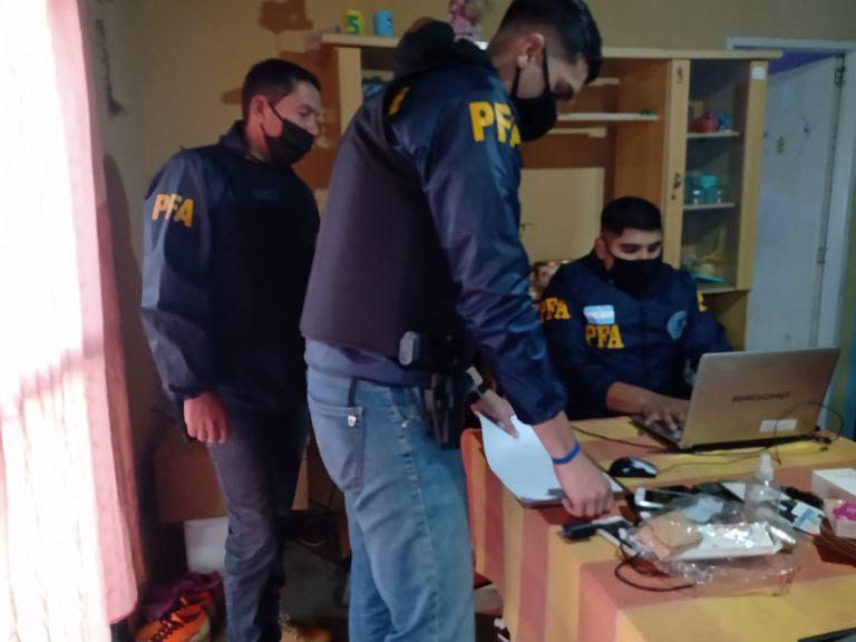 Agentes de la PFA registran datos del operativo mientras se realiza un allanamiento