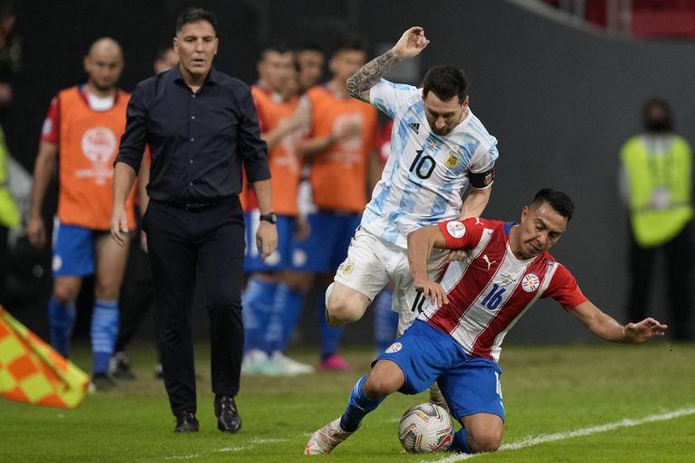 El argentino Lionel Messi, centro, y el paraguayo Angel Cardozo luchan por el balón durante un partido de fútbol de la Copa América en el estadio Nacional de Brasilia, Brasil, el lunes 21 de junio de 2021