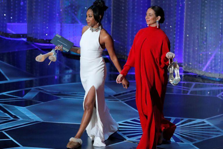 Tiffany Haddish y Maya Rudolph, con sus zapatos en las manos