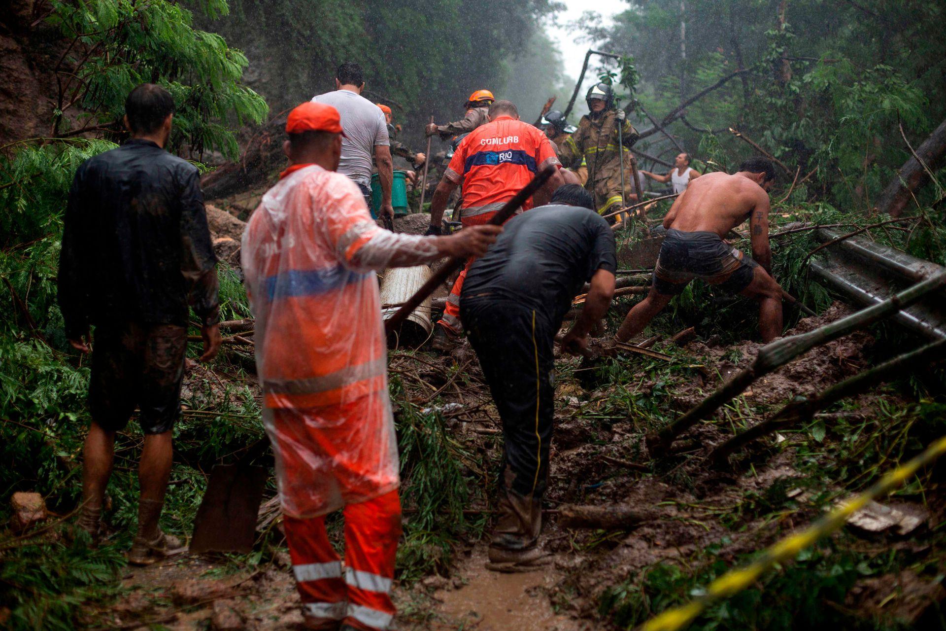 Bomberos, trabajadores municipales, oficiales de policía y voluntarios participan en una operación de rescate después de un deslizamiento de tierra