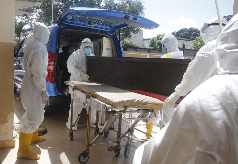 Trabajadores de la salud, equipados con trajes de protección, meten el féretro de una persona fallecida por COVID-19 en una ambulancia antes de enterrarlo, Denpasar, Bali, Indonesia.