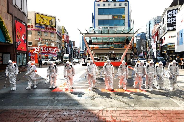 Soldados del ejército de Corea del Sur con trajes protectores rocían desinfectante para evitar la propagación del coronavirus en una calle de Daegu, Corea del Sur