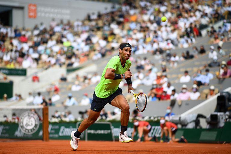 El español Rafael Nadal corre por el balón para devolvérselo al argentino Diego Schwartzman durante el partido de tenis de cuartos de final de individuales masculinos el día 11 del torneo de tenis Roland Garros 2021 del Abierto de Francia en París el 9 de junio de 2021 (Foto de Christophe ARCHAMBAULT / AFP )