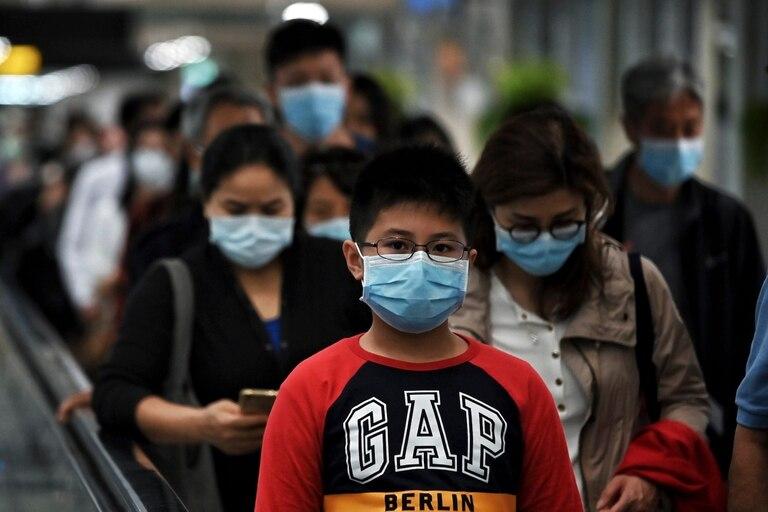 La gente llega con barbijos al aeropuerto de Wuhan