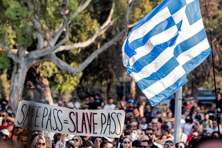 """""""Pase de seguridad=pase de esclavos"""", dice un cartel de manifestantes antivacunas en Nicosia contra el """"pase verde"""" impuesto por el gobierno de Chipre; flamea una bandera de Grecia"""
