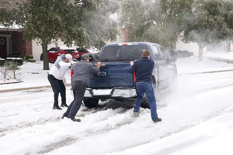 Los residentes ayudan a un conductor a salir del hielo en la carretera en Round Rock, Texas, el 17 de febrero de 2021, después del paso de una tormenta de invierno