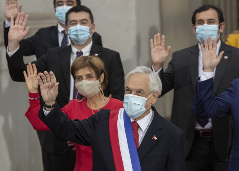 El presidente de Chile, Sebastián Piñera, al centro, y miembros de su gabinete, saludan mientras posan para una foto grupal oficial en el palacio presidencial de La Moneda en Santiago, Chile, el martes 1 de junio de 2021. (AP Foto/Esteban Felix)