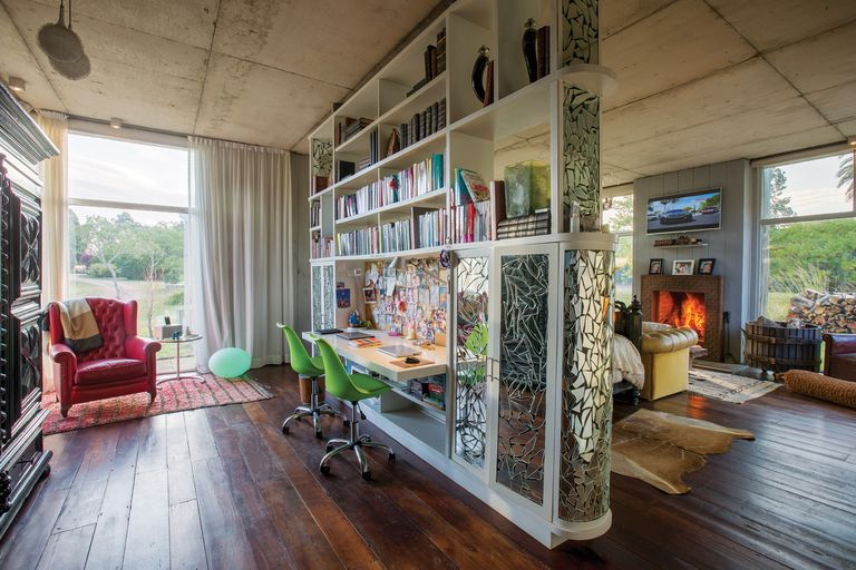Un gran mueble, revestido con un mosaico de espejos rotos, divide el escritorio del dormitorio de los dueños de casa. Al lado de un sillón, donde Javier suele leer, se ve una lámpara Guzzini original.