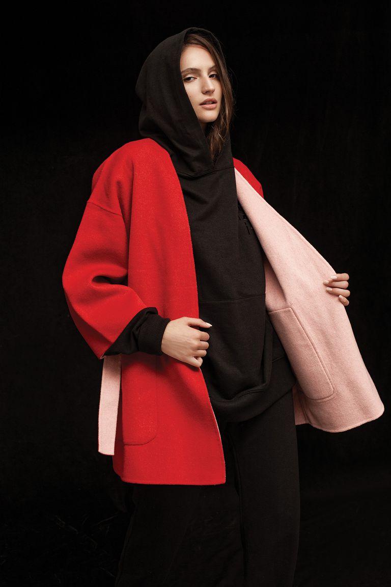 Buzo negro deportivo oversize de algodón con capucha (Levi's), pantalón estilo jogger de algodón (Giesso), tapado de lana reversible con mangas caídas oversize rojo y rosa (Las Pepas)