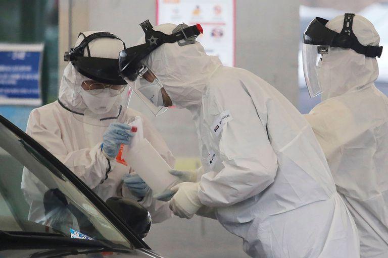 Personal médico con trajes protectores toma muestras de una persona con sospecha de síntomas del nuevo coronavirus en un centro de pruebas de detección de virus en Goyang, Corea del Sur.