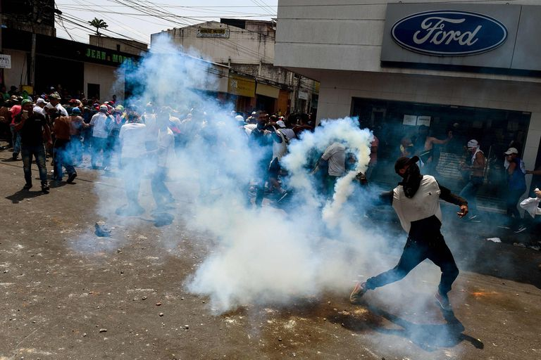 Un manifestante recoge un bote de gas lacrimógeno durante enfrentamientos con las fuerzas de seguridad en una manifestación contra el gobierno de Nicolás Maduro, en San Antonio del Táchira, Venezuela.