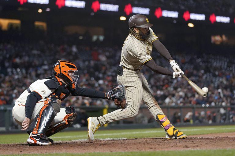 Fernando Tatis Jr., de los Padres de San Diego, conecta un sencillo ante el catcher de los Gigantes de San Francisco, Buster Posey, en el sexto inning del juego de la MLB que enfrentó a ambos equipos en San Francisco, el 15 de septiembre de 2021. (AP Foto/Jeff Chiu)