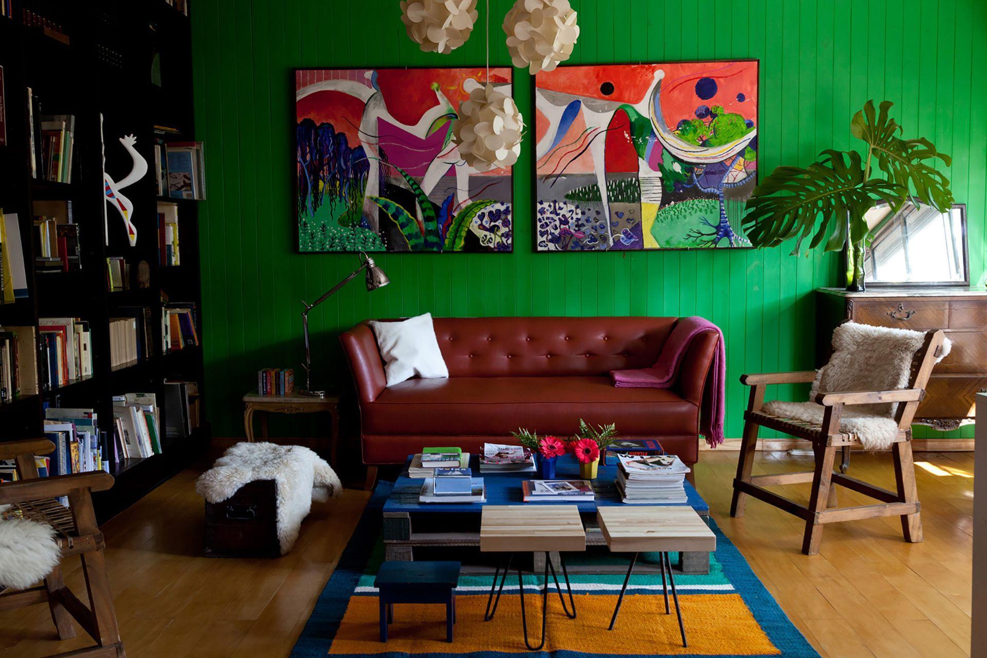 Al entrar a la casa, en la planta baja, aparece el living con la pared de machimbre pintada de verde y dos cuadros de Kalil hechos especialmente para este ambiente.