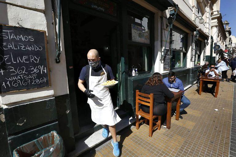 Un mozo con barbijo y guantes acerca el pedido a una mesa, en el barrio de San Telmo