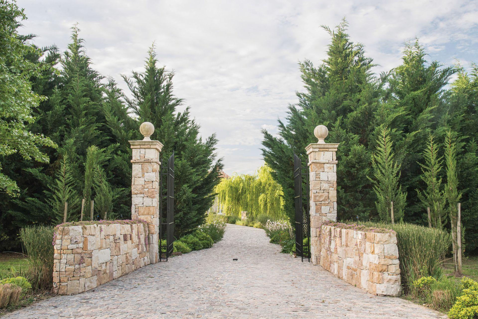 El acceso a la propiedad se realiza a través de un portón de hierro con muretes y columnas de piedra, en donde ya se vislumbra  el estilo de La Toscana.