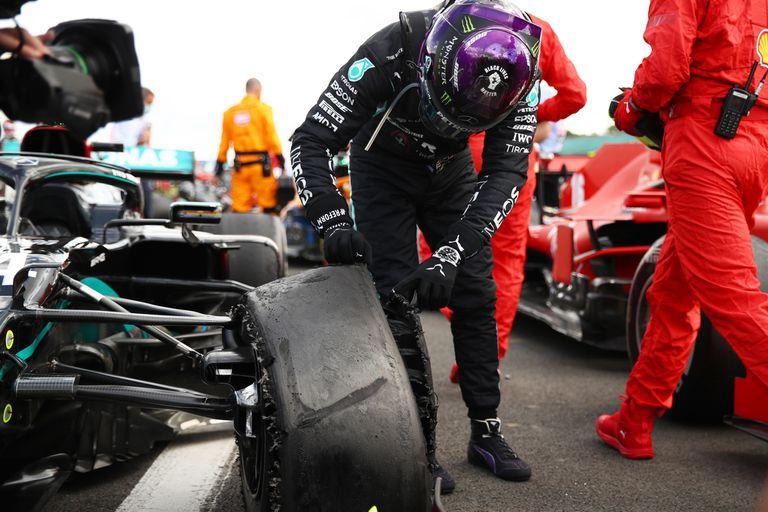 Lewis Hamilton revisa cómo quedó su neumático delantero izquierdo tras bajarse de su auto al final del GP de Gran Bretaña.