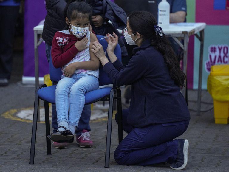 Un trabajador de la salud inocula a una niña contra el COVID-19 en la escuela Providencia en Santiago, Chile, el lunes 27 de septiembre de 2021, durante el inicio de la vacunación en escuelas para niños de 6 a 11 años