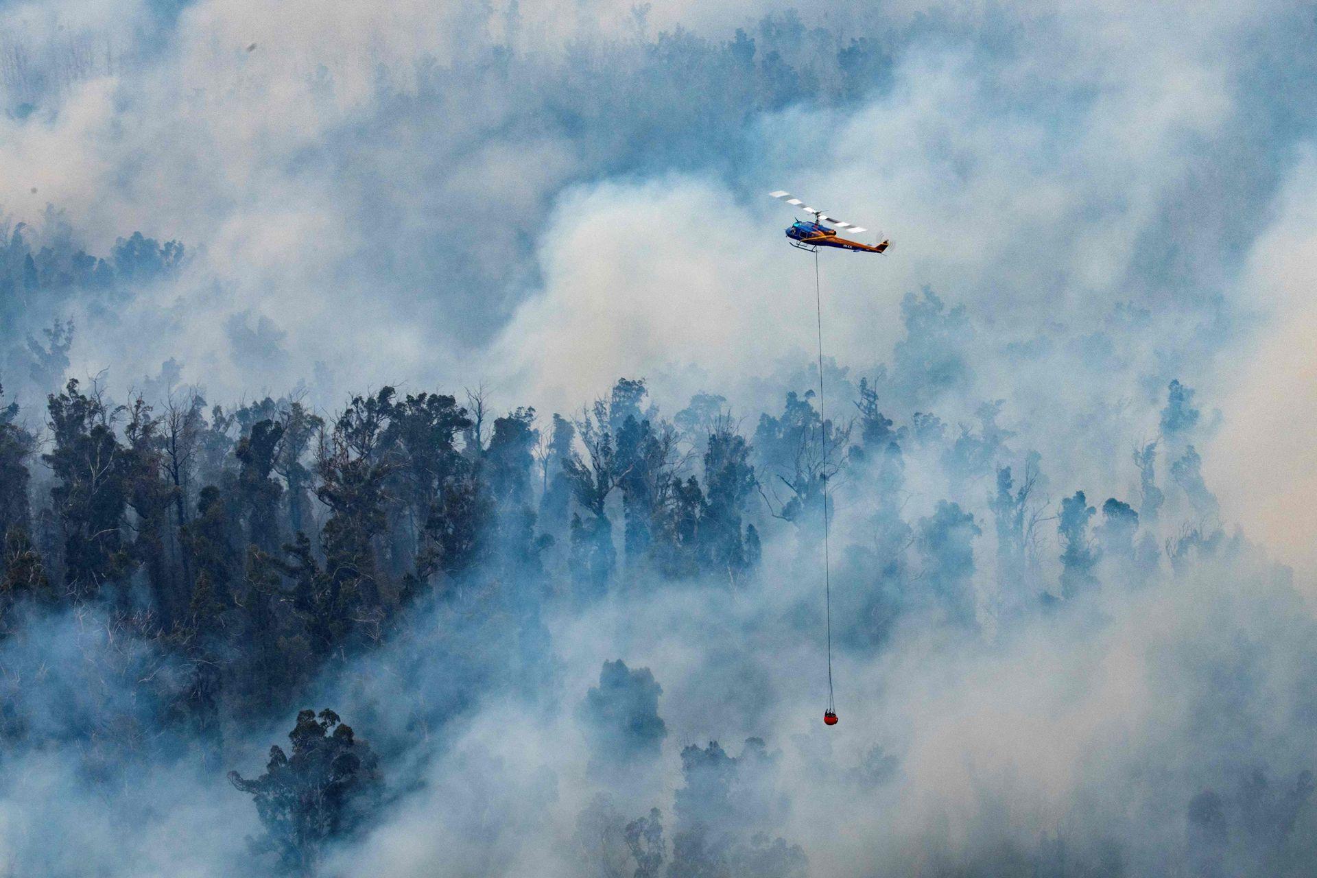 Un helicóptero arroja agua sobre un incendio en la región de East Gippsland de Victoria, el 29 de diciembre de 2019.