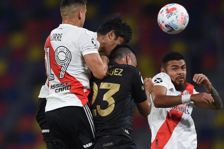 Nery Domínguez, de Racing, intenta cabecear entre varios jugadores de River.