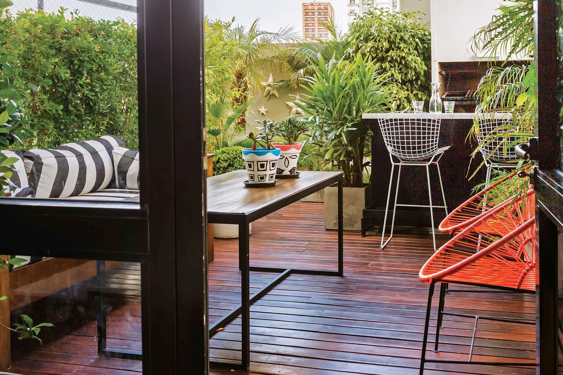 El espacio al aire libre se trazó como un auténtico ambiente, y se organizó en dos zonas: junto a la parrilla, la barra con banquetas 'Bertoia'; cerca de la puerta, un living con sillas 'Acapulco', mesa baja y sillón de madera con almohadones impermeables.