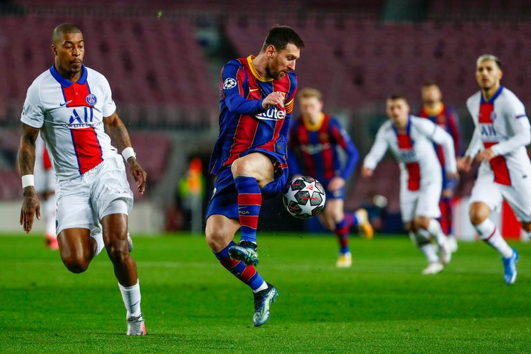 Barcelonas Lionel Messi, right, duels for the balls with PSGs Presnel Kimpembe during the Champions League round of 16, first leg soccer match between FC Barcelona and Paris Saint-Germain at the Camp Nou stadium in Barcelona, Spain, Tuesday, Feb. 16, 2021. (AP Photo/Joan Monfort)