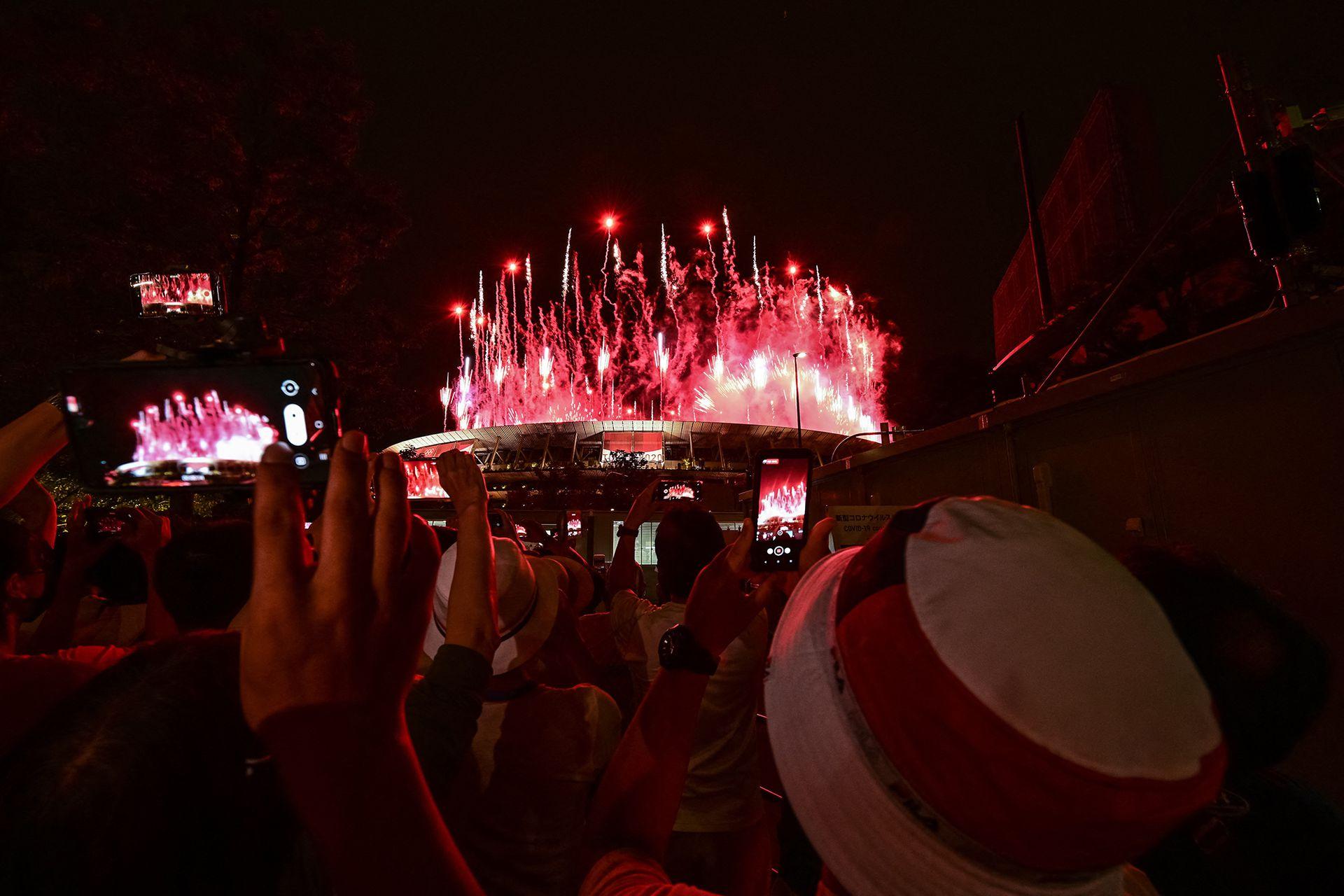 Los aficionados que están afuera toman fotografías de los fuegos artificiales que iluminan el cielo sobre el Estadio Olímpico durante la ceremonia de apertura de los Juegos Olímpicos de Tokio 2020, en Tokio, el 23 de julio de 2021.