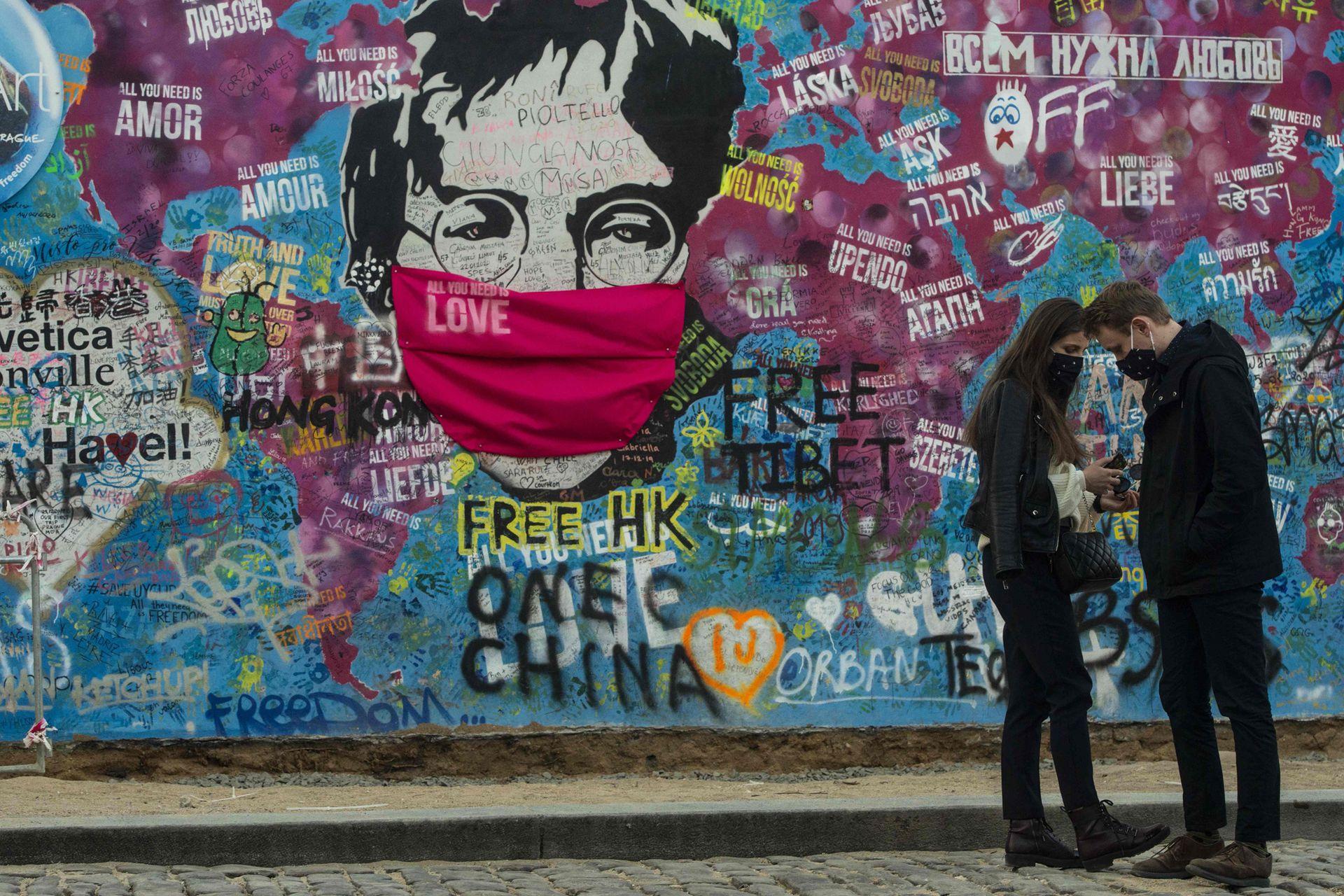 """Una pareja se para frente al """"Muro de Lennon"""" con un barbijo de tela adherido a la imagen en Praga"""