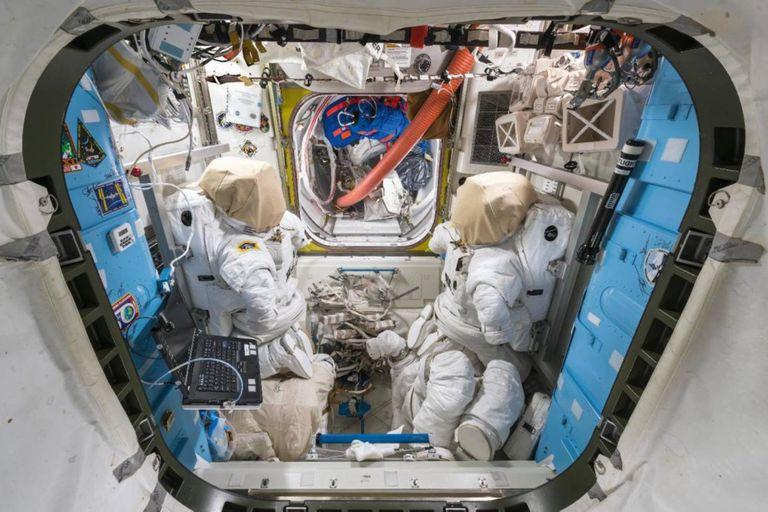 Una de las escotillas para salir al espacio exterior y dos trajes de astronautas
