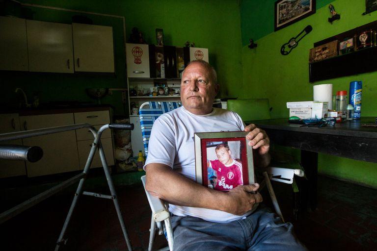Jorge Rego, en su casa, con la foto de su hijo, Cristopher, y las paredes y los estantes que muestran la pasión de ambos por Huracán