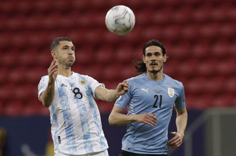 Guido Rodríguez se posiciona para controla la pelota ante Edinson Cavani