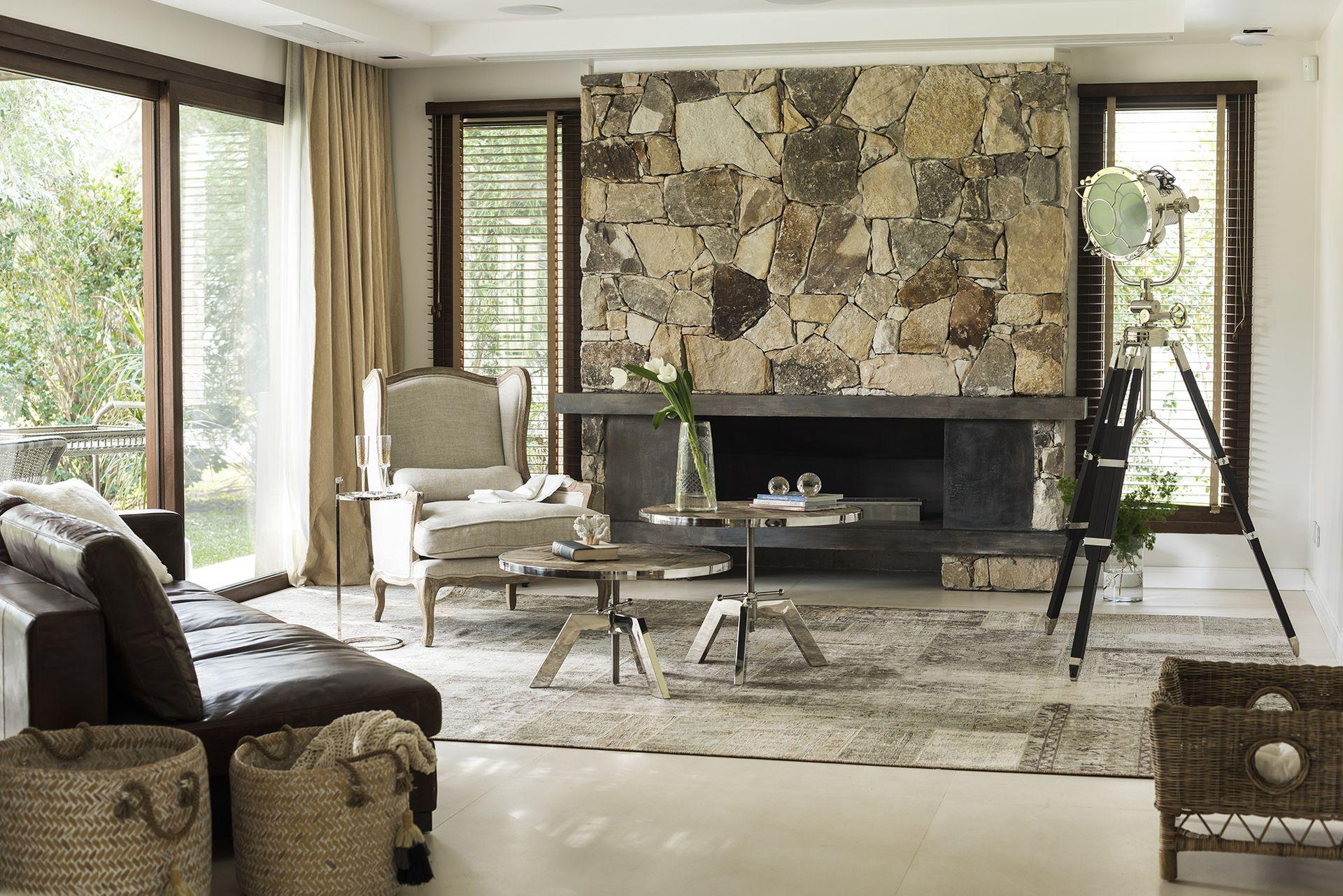 En el living, sillón 'Marseilles' de roble platinado y lino, sofá 'Lincoln' de cuero, mesas ratonas de altura regulable con patas cromadas y tapa de roble, y lámpara trípode 'Allen Good' (todo de Landmark) sobre alfombra patchwork 'Persia' (Mihran).