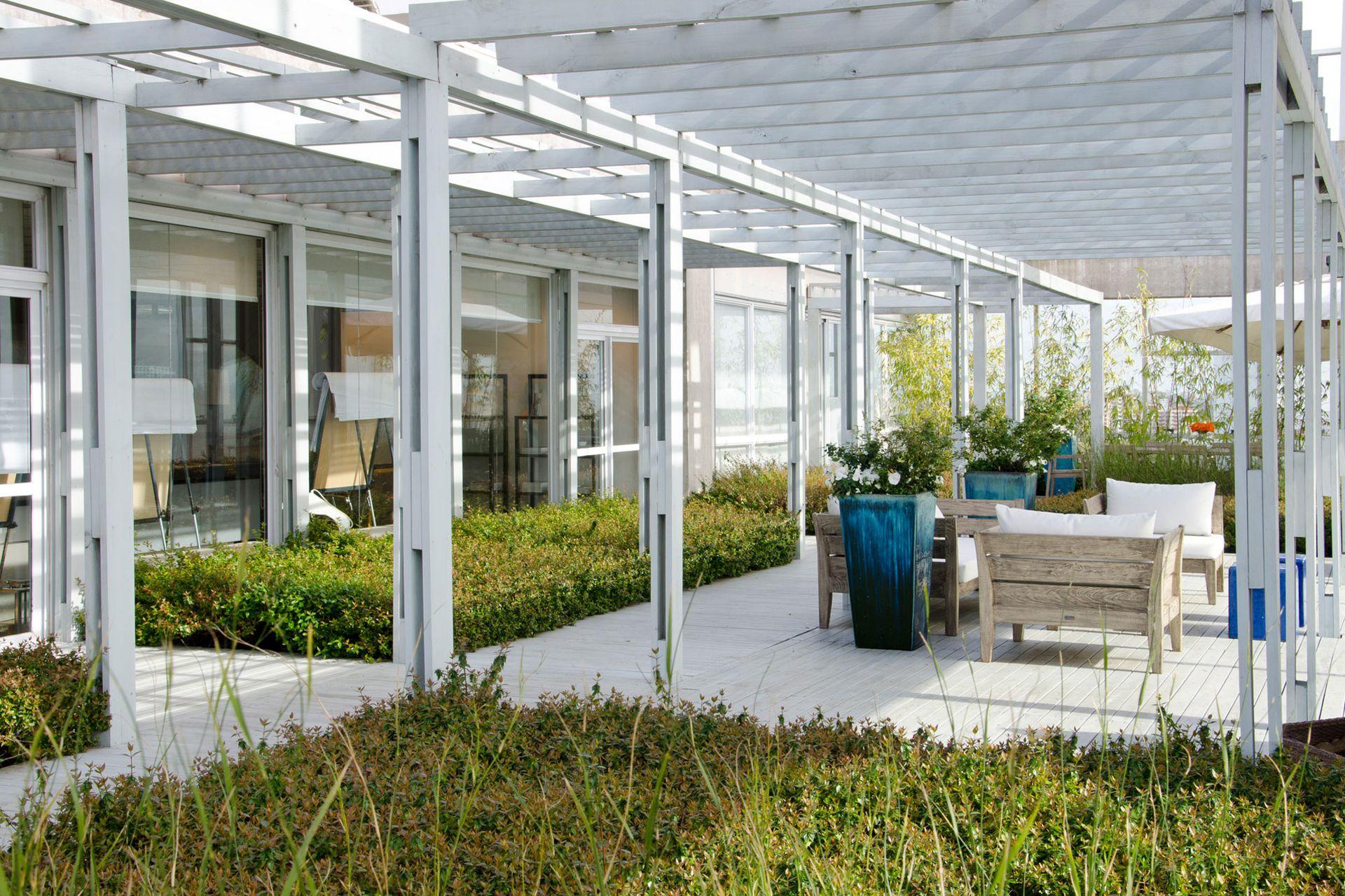 Mucho verde y una pérgola blanca definen el estilo despojado de esta terraza, en la que se contempló la inclusión un living con sillones. (Paisajismo: Lucía  Schiappapietra y Asoc.)